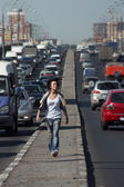 Girl goes on highway middle in city — Stock Photo