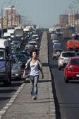 Mädchen geht auf autobahn mitten in der stadt — Stockfoto
