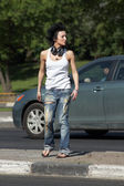 Girl with ear-phones stands on road among cars — Стоковое фото