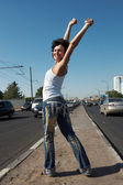 Girl with lifted hands stands in half-turn on middle of road amo — Stock Photo