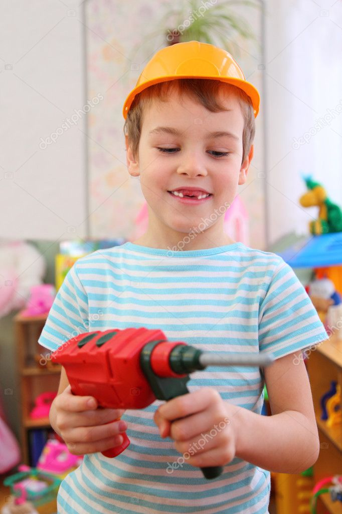 Boy in plastic helmet with toy drill  Stock Photo #7423435