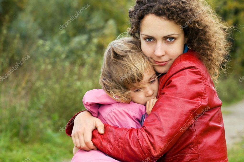 Young woman protects little girl from wind in garden — Stock Photo #7426795