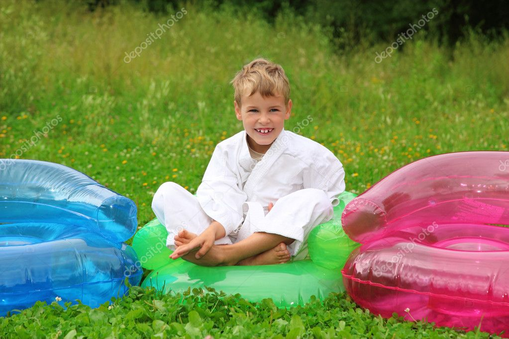 Karate Boy Sits In Inflatable Armchair On Lawn Stock