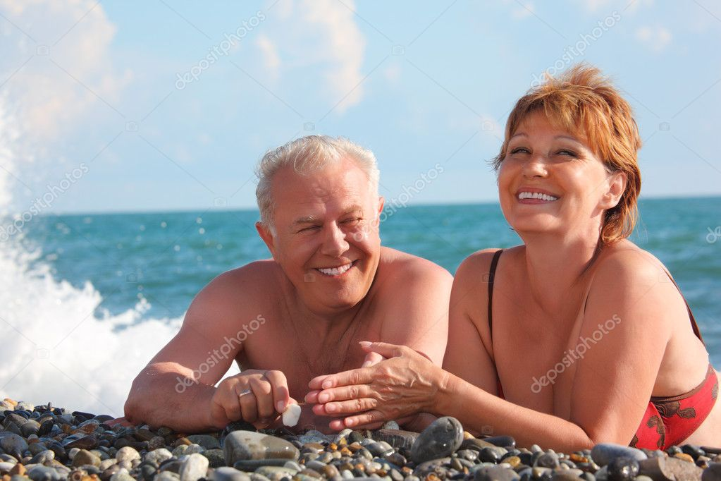 Happy aged pair lie on pebble beach, focus on man, woman in little motion blur  Stock Photo #7429269