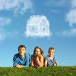 Family with boy on grass and dream cloud house collage — Stock Photo