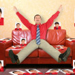 Man on the leather red sofa with the photographs, collage — Stock Photo