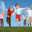 Many jumping children on grass, collage — Stock Photo #7430056