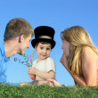 Child in a hat with a mother and father on a grass, collage - Stock Photo