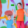 Son and mother draw with rollers and brushes on a wall, collage - Stock Photo