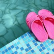 Beach slippers on pool side — Stock Photo