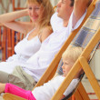 Happy family with little girl reclining on chaise lounges on ver — Stock Photo