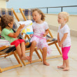 Three little girls in lounge on veranda, considering drawing - Stock Photo