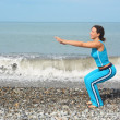 Woman is making exercise on sea coast - Stock Photo