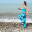 Woman is making exercise on sea coast — Stockfoto