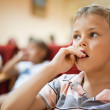 Boy sitting in cinema armchair, holding fingers near mouth — Stock Photo #7430539