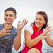 Smiling man and young beautiful women dancing sitting on beach — Stock Photo