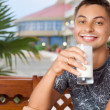 Young smiling man sitting in an arbour on resort, drinking kefir - ストック写真