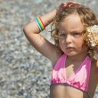 Pretty little girl has leant seashell bowl to an ear on seacoast - Stock Photo