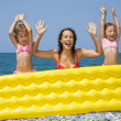 Young woman and two little girls standing behind an inflatable m — Stock Photo #7430674