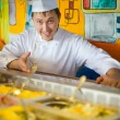 Cheerful cook in uniform near counter with meal — Stockfoto