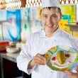 Cheerful cook in uniform holding in hands dish with salad in for — Stok fotoğraf