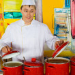 Cheerful cook in uniform near red pans in public catering restau — Stock Photo