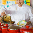 Stock Photo: Cheerful cook in uniform spoon imposes soup in plate in public c