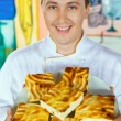 Cheerful cook in uniform holding cheese baked pudding on dish — Foto Stock