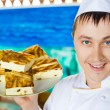 Cheerful cook in uniform holding cheese baked pudding on dish — ストック写真