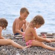 Children three together sitting on stony beach, creates pyramid — Stock Photo