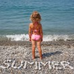 Little girl sits on beach — Stock Photo