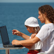 Family resting on sea with laptop - Stockfoto