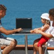 Family resting on sea with laptop — Stock Photo #7430893