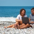 Man and girl on seashore with laptop - Stock Photo