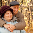 Old man and old woman in autumnal forest — Stock Photo #7430945
