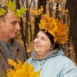 Old man and old woman in autumnal forest — Stock fotografie