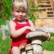 The girl on a lawn sits with a toy mushroom — Stock Photo