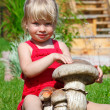 The girl on a lawn sits with a toy mushroom — Stock Photo #7431080