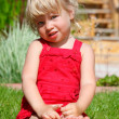 The little girl sits on a lawn — Stock Photo