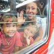 Mother and children look from train window — Stock Photo