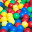 Multi-coloured balls float on water - Stock Photo