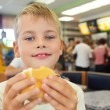 Stock Photo: Boy eats hamburger