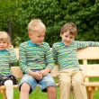 Three children on a bench in identical clothes — Stock Photo #7431160