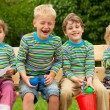 Four children in identical clothes laugh sitting on a bench. — Stock Photo