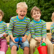 Four children in identical clothes laugh sitting on a bench. — ストック写真