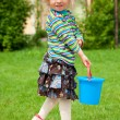 The girl in a garden with a toy bucket — Stock Photo