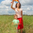 Young woman and little girl plays kite on meadow — Stock Photo #7431166