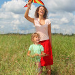 Royalty-Free Stock Photo: Young woman and little girl plays kite on meadow