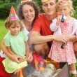 Happy family with children near brazier on picnic, happy birthda — Stock Photo