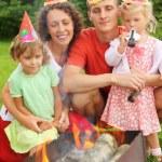 Happy family with children near brazier on picnic, happy birthda — Stock Photo #7431199